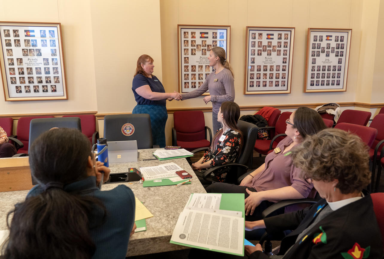 Getting Green Laws attendees watch Jen Boulton and Abby Burk demonstrate a legislator meeting at the lobby day in the Colorado Capitol.