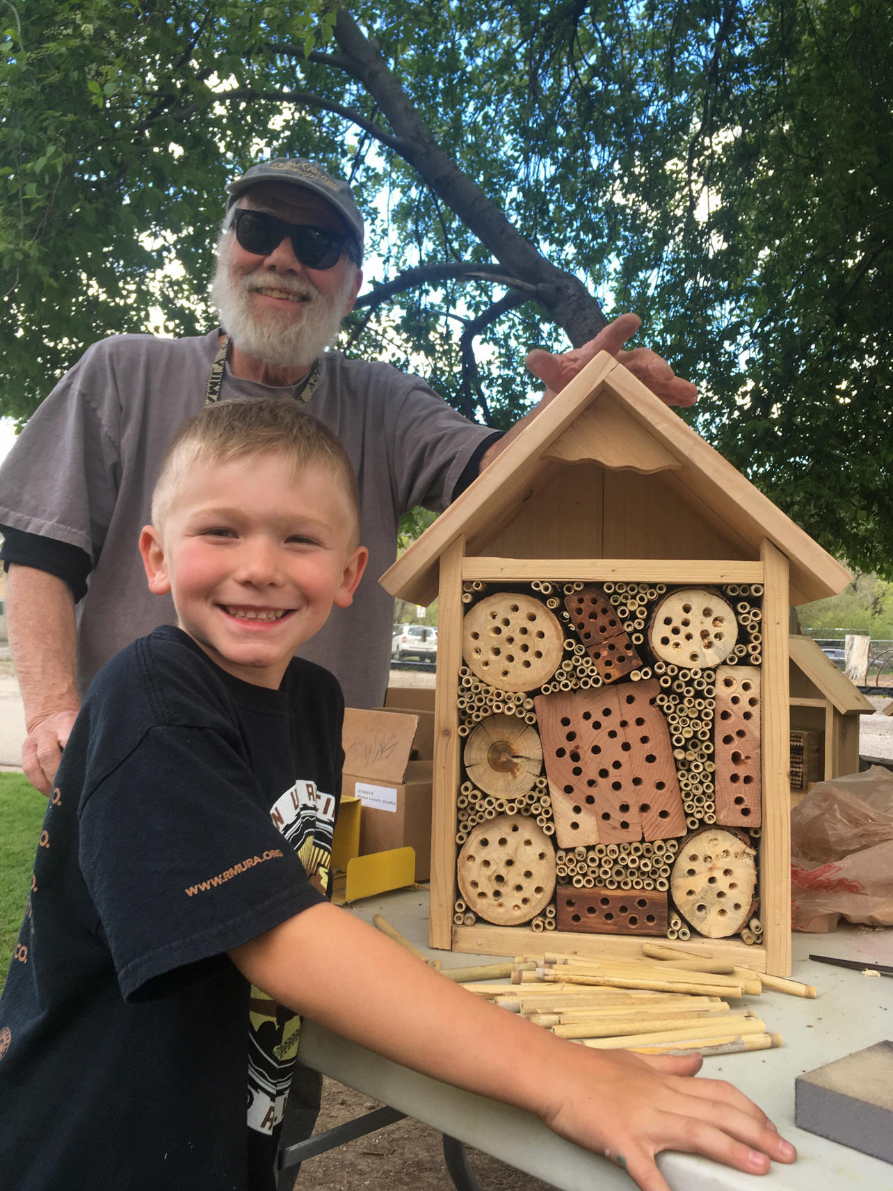 Jim Lutomski, a regional artist and design contributor to the project, and a Pagosa Family School student with a pollinator structure. student from .