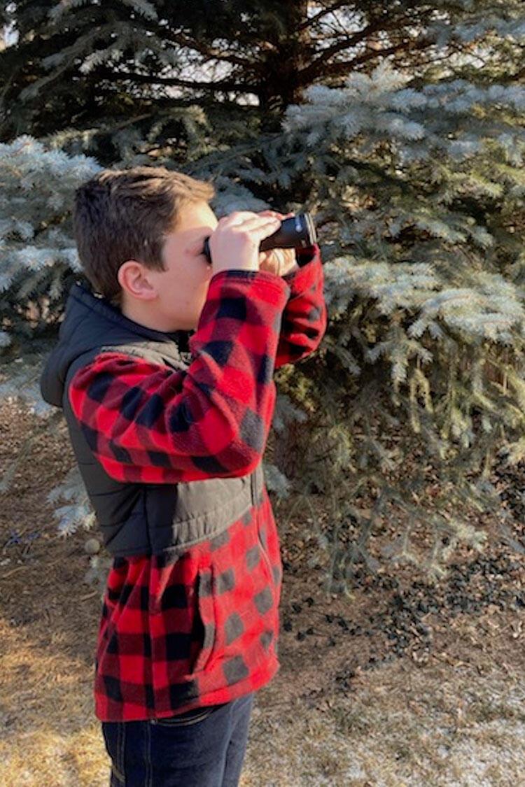 Ian looks through a pair of binoculars.