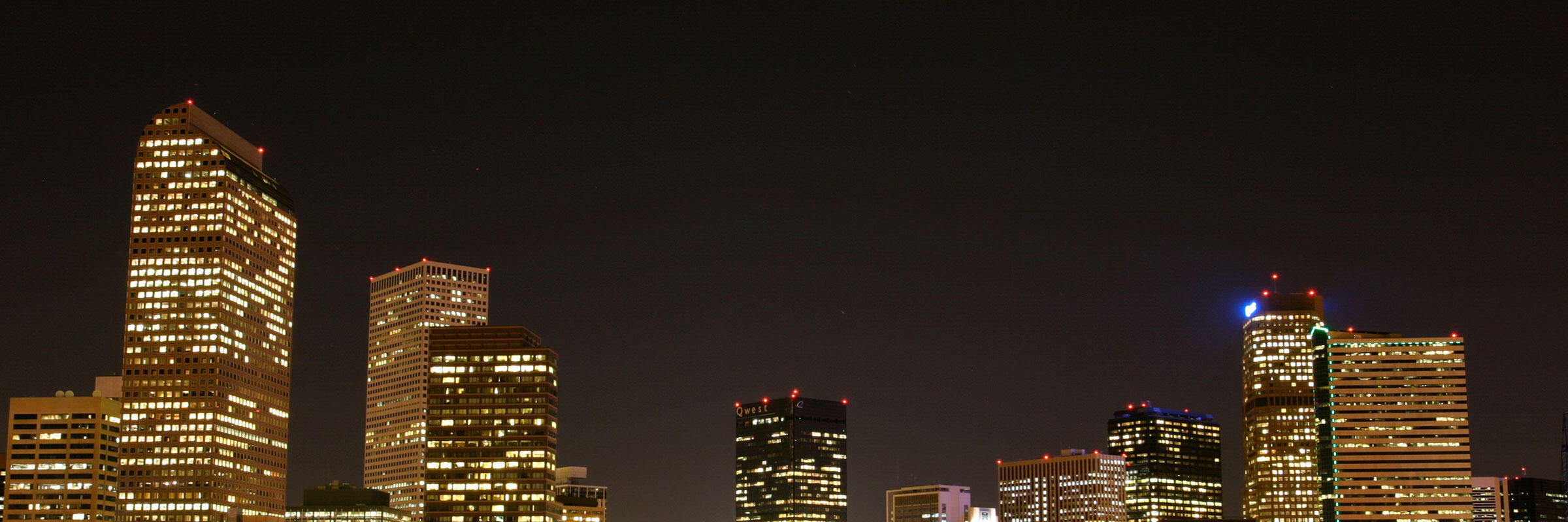 Buildings lit up at night in Denver.