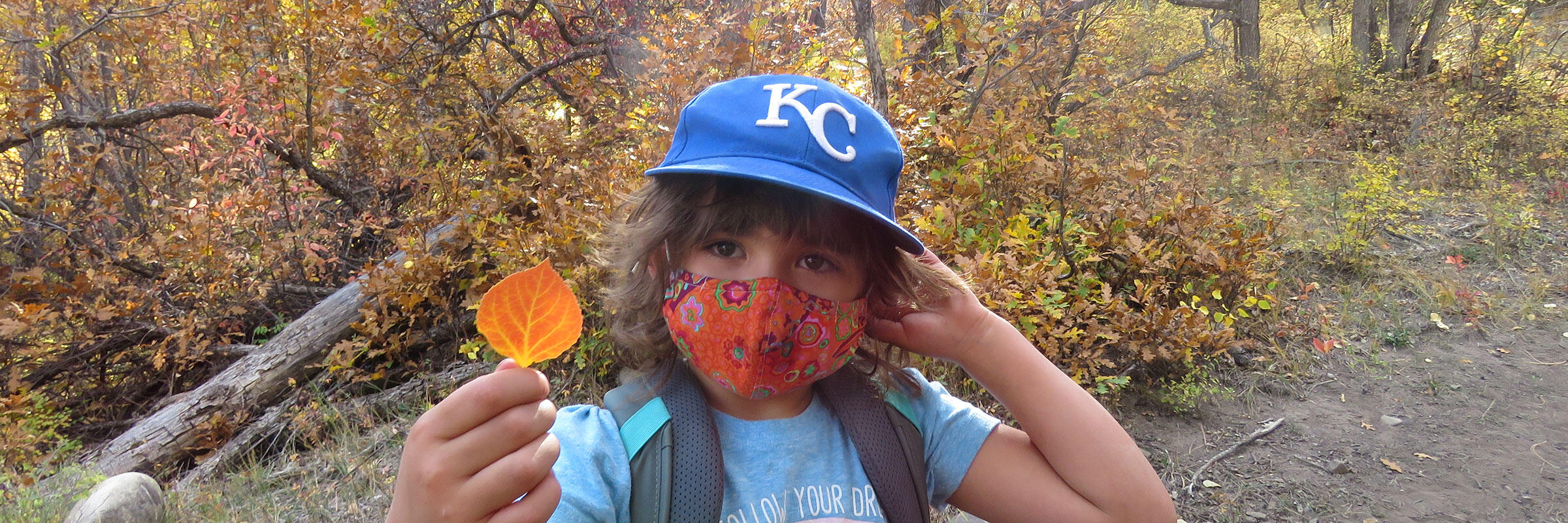 A girl holds a leaf during a Friday at Four Mile Ranch event.