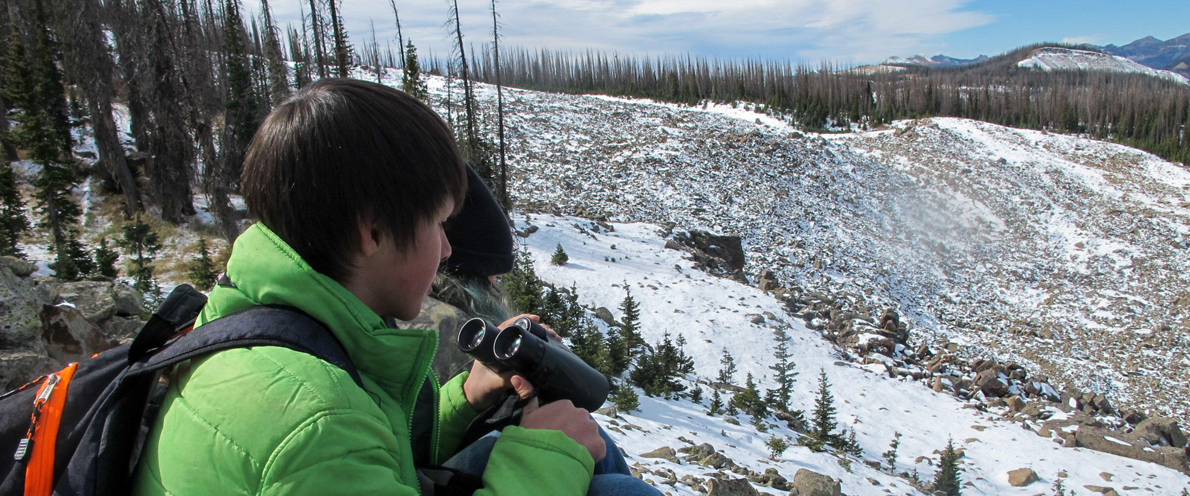 A boy looks for pikas in the mountains
